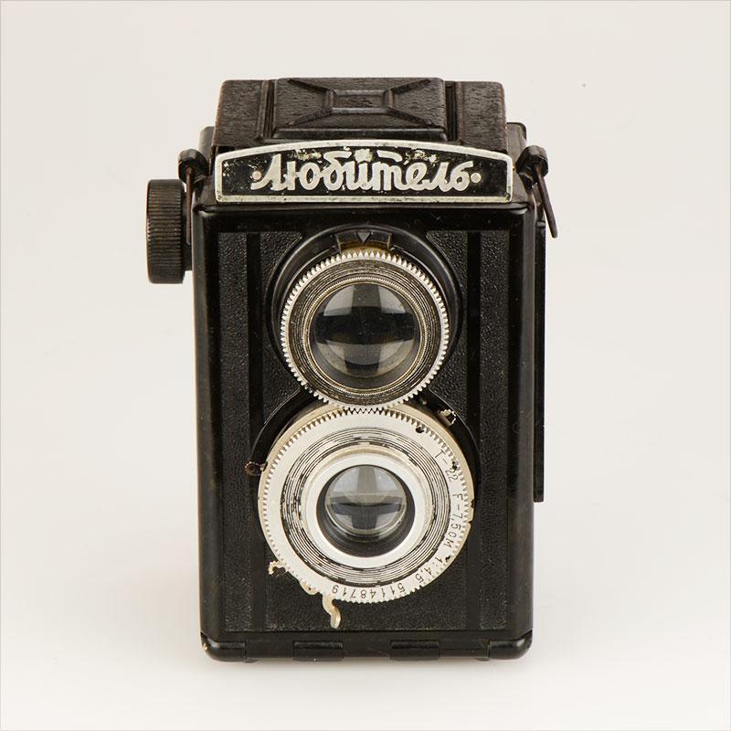 Lubitel (俄语: , 有业余的意思) LOMO生产的几款中画幅双镜头反光相机在设计上是模仿福伦达早期1930的Brilliant相机,并施以一定的改进。该相机使用120胶卷,镜头和快门组合从B门到1/250秒,光圈F4.5--22。3片玻璃镜片在光圈小时可以得到相当好的成像,但在大光圈时, 以今天的标准看,成像显得不够硬。该机的调焦相比福伦达Brilliant相机的分段估计对焦得到很大的改善,可以准确人工对焦。